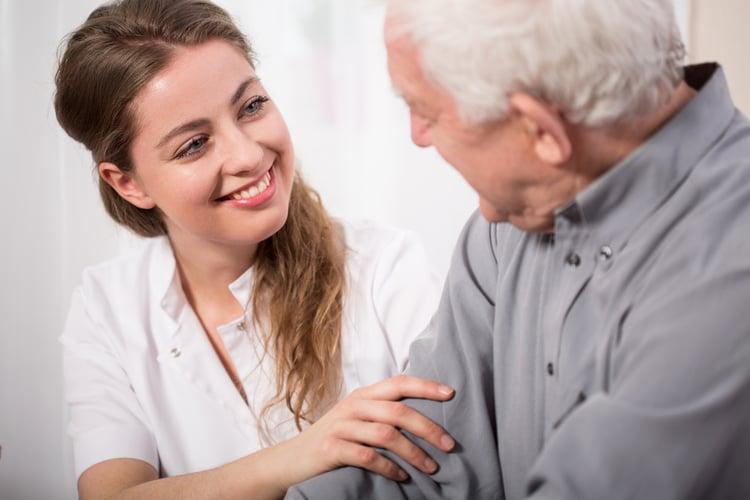 Picture of smiling nurse assisting senior man